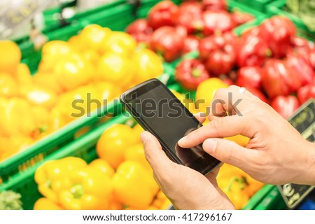 Man hand digiting on mobile smart phone touchscreen - Online shopping concept with electronic products purchase through smartphone dedicated app - Modern lifestyle with technology in everyday life - stock photo