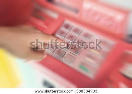 Man Hand entering PIN numbers on ATM bank machine blur background - stock photo
