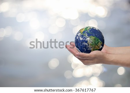 man hand gesture palm up holding world on blurred peaceful landscape water surface background:safe earth energy concept:people and ecology efficiency:healthcare of planet resource:help global together - stock photo