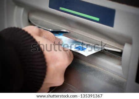 Man hand getting 20 euro banknotes at ATM machine in the street. - stock photo