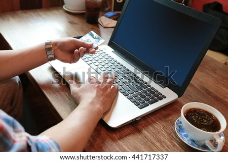 man hand hold credit card on laptop, Online payment, vintage tone - stock photo
