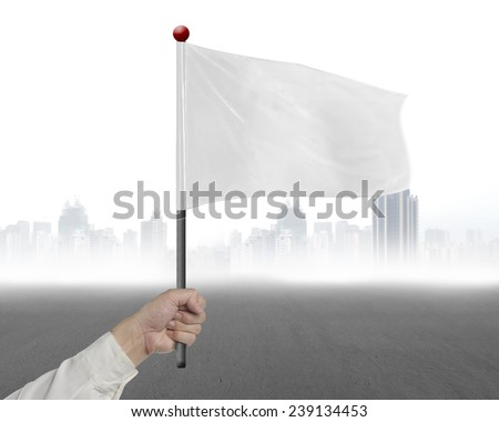 man hand holding blank white flag with gary cityscape background - stock photo