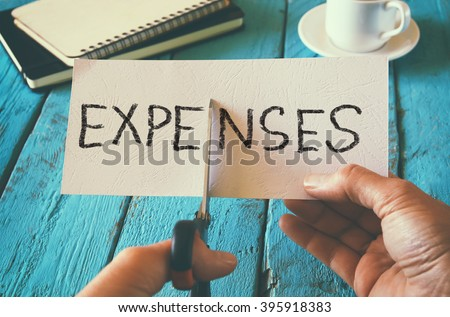 man hand holding card with the word expenses. cutting expenses and costs concept. retro style image - stock photo