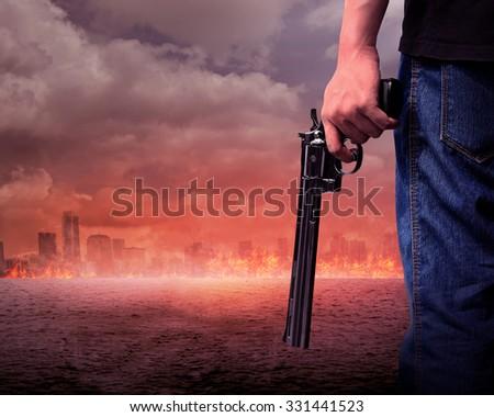 Man hand holding gun with burn city background - stock photo