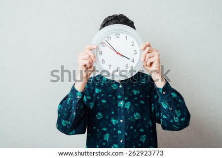 Man hand holding large office wall clock showing time - stock photo