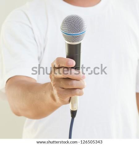 Man hand holding  microphone - stock photo