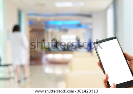 Man hand holding mobile smart phone and blurred figures of doctors and nurses in a hospital corridor. - stock photo