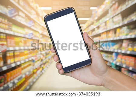 Man hand holding mobile smart phone , tablet,cellphone over Blur of  backgrond with  shopping center or super market background.shopping online.vintage photo - stock photo
