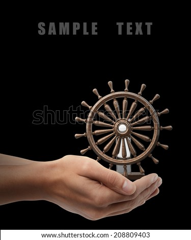 Man hand holding object ( wooden steering-wheel ) isolated on black background. High resolution  - stock photo