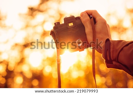 Man hand holding retro photo camera outdoor hipster Lifestyle with sun lights bokeh autumn nature on background - stock photo