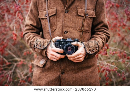 Man hand holding retro photo camera outdoor Lifestyle concept with  autumn nature on background - stock photo