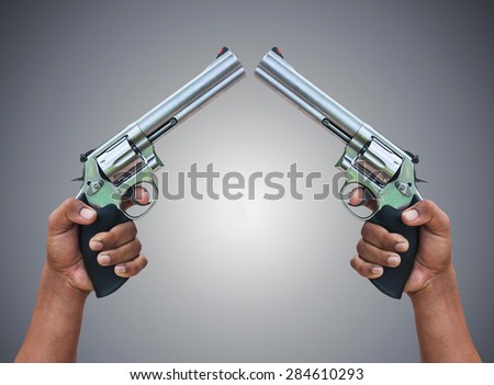 man hand holding revolver on gray  background - stock photo