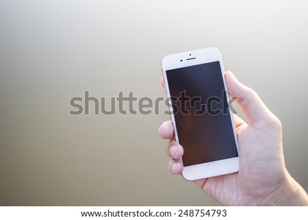 Man hand holding smartphone against on smooth background. - stock photo
