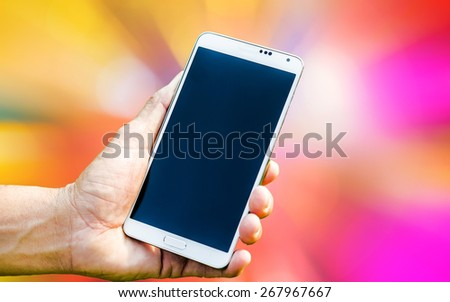Man hand holding smartphone on apstract blured of background soft focus. - stock photo