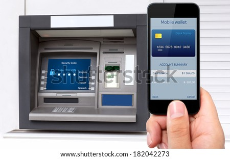 man hand holding the phone with mobile wallet and credit card on the screen against the background of the ATM - stock photo