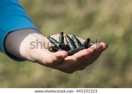 man hand holding used shells on green - stock photo