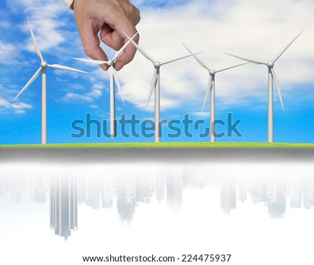 man hand holding windmills in a line with city buildings reflection on sky background - stock photo