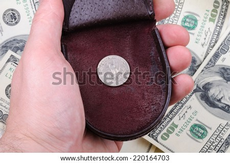 Man hand holds old purse with one quarter coin against background of hundred dollars banknotes. - stock photo