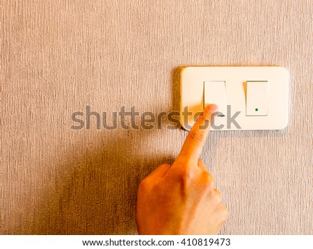 Man hand on light switch, cool color filter - stock photo