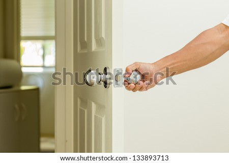 Man hand open door knob - stock photo