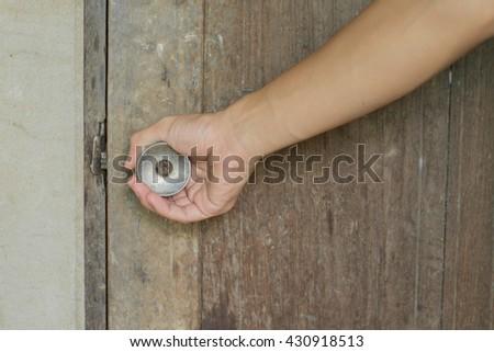 Man hand open door knob,Man hand open old door. - stock photo