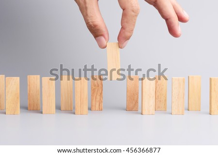 Man hand pick one of wood block from many wood block in row, metaphor to business concept in choose ideal person from many candidate. Gray background, side view. - stock photo