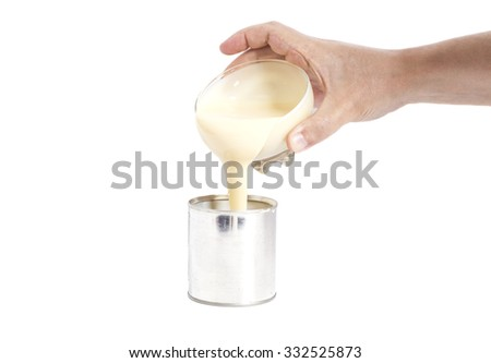Man hand pouring condensed milk into a tin can isolated - stock photo
