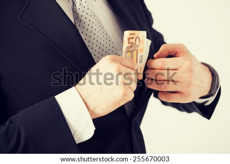 man hand putting euro cash money into suit pocket - stock photo