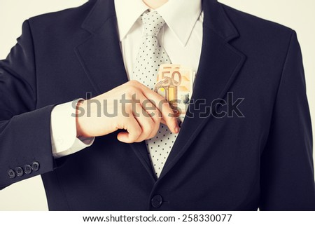 man hand putting euro cash money into suit pocket - stock photo