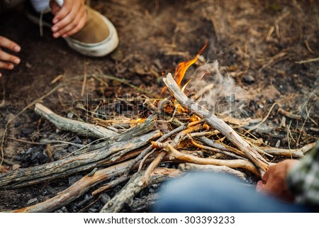 man hand putting fir wood to fire - stock photo