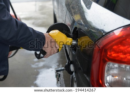 man hand refilling up gas tank of the car with green eco fuel on a filling station - stock photo