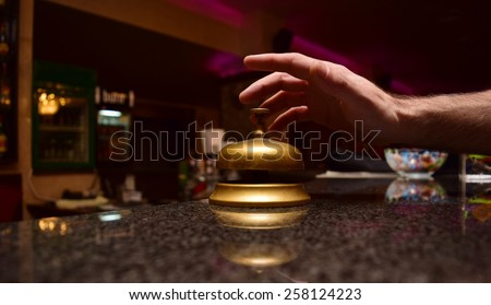 man hand ring the bell at the hotel front desk - stock photo