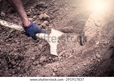 man hand shoveling the soil on garden,vintage filter - stock photo