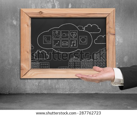 Man hand showing blackboard with hand-drawn app icons hanging on concrete wall - stock photo