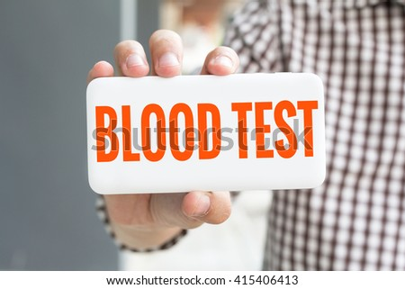 Man hand showing BLOOD TEST word phone with  blur business man wearing plaid shirt. - stock photo