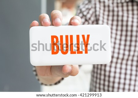 Man hand showing BULLY word phone with  blur business man wearing plaid shirt. - stock photo