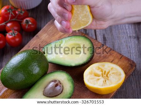 Man hand squeezing lemon on avocado. - stock photo