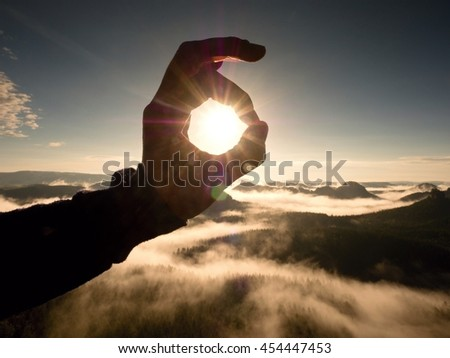 Man hand touch Sun. Misty daybreak in a beautiful hills. Peaks of hills are sticking out from foggy background, the fog is red and orange due to Sun rays. Lens defects. - stock photo