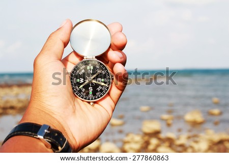 Man hand with a black and silver compass in a beach - stock photo
