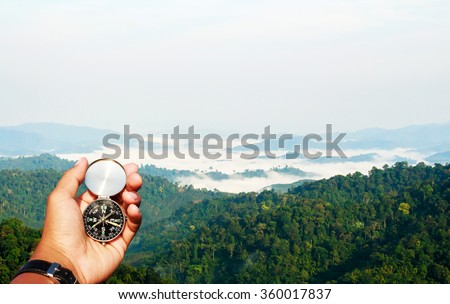 Man hand with a black and silver compass in green  mountain blur. - stock photo