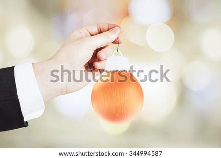 Man hand with christmas tree toy - orange ball - stock photo