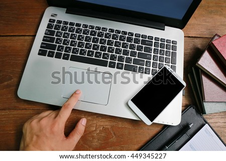 man hand working on phone and laptop on wooden table with relaxing feeling, man working on his laptop in a coffee shop, businessman hand busy using laptop at office desk,nice responsibility lifestyle  - stock photo