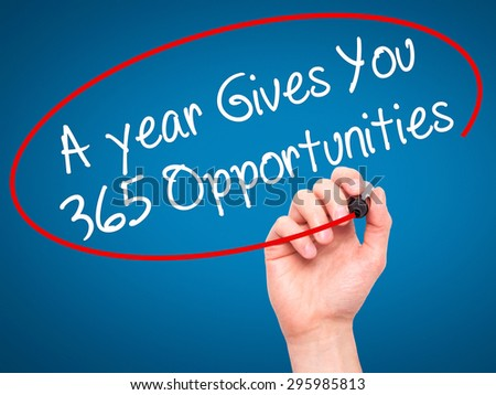 Man Hand writing A year Gives You 365 Opportunities with black marker on visual screen. Isolated on blue. Business, technology, internet concept. Stock Photo - stock photo