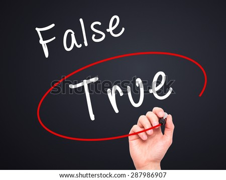 Man Hand writing an choosing True instead of False with black marker on visual screen. Isolated on black. Business, technology, internet concept. Stock Image - stock photo