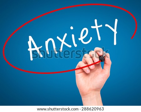Man Hand writing Anxiety with black marker on visual screen. Isolated on blue. Business, technology, internet concept. Stock Image - stock photo