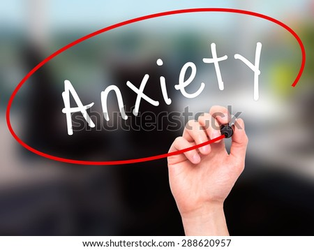 Man Hand writing Anxiety with black marker on visual screen. Isolated on office. Business, technology, internet concept. Stock Image - stock photo