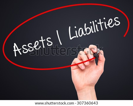 Man Hand writing Assets Liabilities with black marker on visual screen. Isolated on black. Business, technology, internet concept. Stock Photo - stock photo