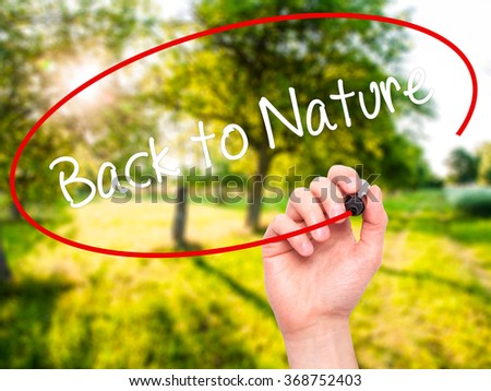 Man Hand writing Back to Nature with black marker on visual screen. Isolated on background. Business, technology, internet concept. Stock Photo - stock photo