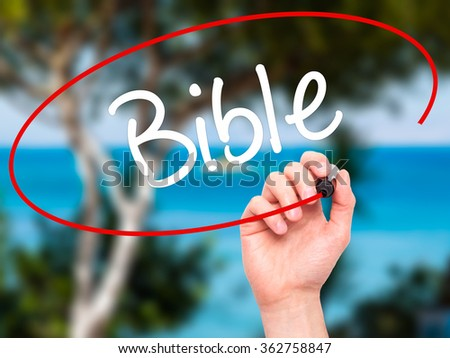Man Hand writing Bible with black marker on visual screen. Isolated on background. Business, technology, internet concept. Stock Photo - stock photo