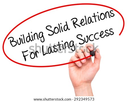 Man Hand writing Building Solid Relations For Lasting Success with black marker on visual screen. Isolated on white. Business, technology, internet concept. Stock Image - stock photo